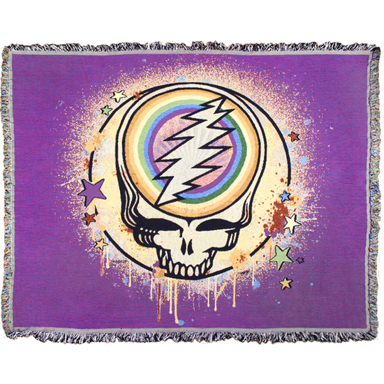 A violet woven cotton blanket with a Grateful Dead Steal Your Face Skull, with a full circle rainbow in the center of the skull, spray paint splatters filling in the circle around it, and dripping around the edges, and stars scattered around the edges of the circle.