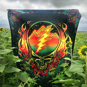 The Scarlet Fire fleece blanket being held up in a field of sunflowers.
