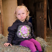 A curly-haired toddler sitting on a bale of hay, making a scrunched up face at the camera and wearing a dark grey Sugar Magnolia toddler hoodie.