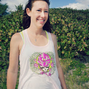 A smiling woman standing in grassy sand in front of large bushes, wearing a pink Sugar Magnolia women's flowy racerback tank.