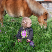 A curly-haired toddler girl sitting in a field, looking back at the miniature horse behind her, wearing a dark grey Sugar Magnolia toddler hoodie.