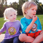 A toddler girl wearing a purple Rainbow Splatter Steal Your Face toddler tshirt, sitting next to a young boy wearing a turquoise Dreamcatcher Steal Your Face tshirt.
