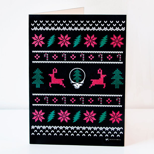 "A vertical black greeting card greeting card in the style of an ugly Christmas sweater. The center row has a white Grateful Dead Stealie with a green Christmas tree in the middle, with a red reindeer on either side of it then green Christmas trees on the outside, a pattern of red and white candy canes and red diamonds are above and below them, then a row of alternating red flowers and green lightning bolts, and rows of white ""stitched"" V's are at the top and bottom."