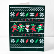 "A black vertical greeting card in the style of an ugly Christmas sweater, with five red, green and white Grateful Dead bears dancing across the center, dressed as Santas, elves, and  a reindeer, a pattern of red and white candy canes and red diamonds above and below them, alternating white flowers and red and green lightning bolts next, and then white ""stitched"" V's in alternating rows to the top and bottom edge."