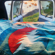 The blue Grateful Owl blanket spread on a van bed, with the back doors open overlooking a grassy shoreline