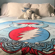 A straight ahead view of the Grateful owl blanket on a bed with white pillows and a stuffed bear at the top