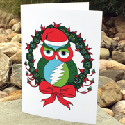 The Holiday Owl greeting card standing upright in front of large river rocks, with long grass in the background