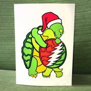 A white vertical greeting card with two terrapin turtles hugging. The bigger one is facing forward and wearing a Santa cap, and the smaller one shows the Grateful Dead lightning bolt on it's shell.