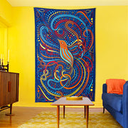 The Hummingbird Tapestry hanging on a bright yellow wall in a room with wooden retro furniture and a bright blue couch with an orange throw pillow