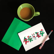 A close up aerial view of the Jingle Bears greeting card with a green envelope and a red pen, on a black surface, next to a half-filled green coffee cup
