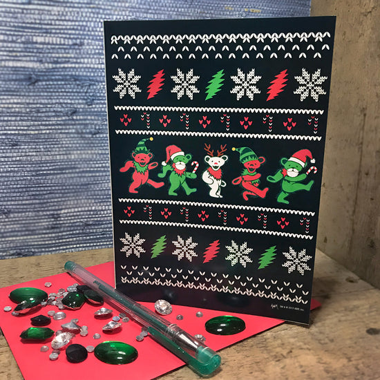 The Ugly Christmas Sweater Jingle Bears greeting card standing upright on a red envelope with a green pen and green and white rhinestones on the envelope