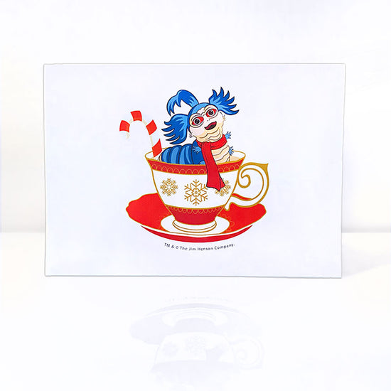 A white greeting card with a smiling blue worm that has a white face and underbelly, with red eyes, three large tufts of hair on his head, wearing a red scarf and sitting in a red and white teacup with a candy cane