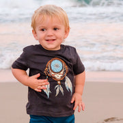 Blonde toddler boy smiling on the beach, wearing the black toddler Dreamcatcher Stealie tshirt