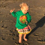 Little girl dancing on a beach wearing the elephant rainbow skirt and a Scarlet Fire Stealie toddler hoodie