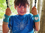 Young boy on a swing, wearing a neon blue youth tshirt with mandala inspired infinity design