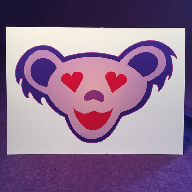 A light purple smiling Grateful Dead bear head with a dark purple outline and ears, red heart eyes, and a red mouth, on a white horizontal greeting card.