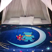 The blue Grateful Dead Moon Swing blanket spread across a queen bed, with white pillows at the top, and white mosquito netting draped at the head of the bed