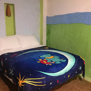 The blue Moon Swing blanket being used as a comforter on a bed in the corner of a room with hand-painted blue, green and white walls.