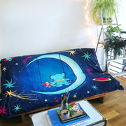 The blue Moon Swing blanket draped on a futon, with a coffee table in front of it, and a ladder with potted plants on the rungs next to it.