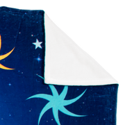 A close up view of the corner of the blue Moon Swing blanket, with the tip turned over to show the white back side.