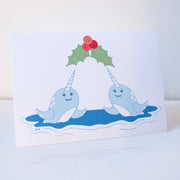 A white horizontal greeting card with two smiling narwhals coming out of the water under mistletoe