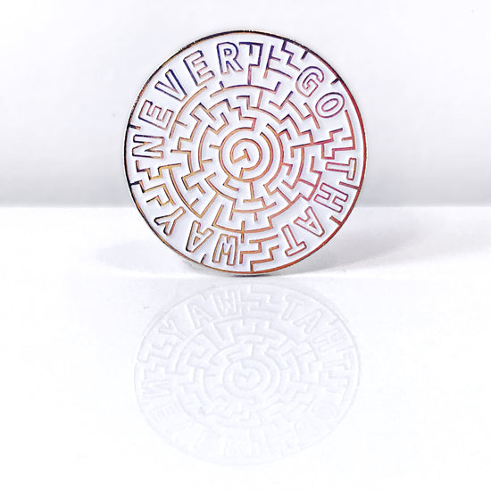 "A round pin with white enamel pin, with a labyrinth design and the words ""Never go that way"" around the outside edge in gold metal"