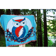 A blue Grateful Owl cotton woven blanket being held up for display in the woods