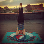 Hippie girl doing a rooftop yoga headstand on a blue Grateful Owl cotton woven blanket