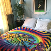 The Rainbow Bears fleece blanket on a bed in the corner of a room, next to a window with the sun shining in on it and a Grateful Dead poster hanging at the head of the bed.