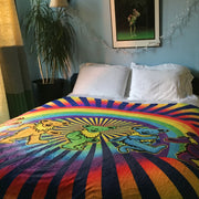 The Rainbow Bears fleece blanket being used as a bed spread, with white pillows in a cheery blue room, with a Grateful Dead poster hanging above it.