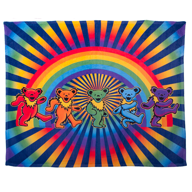 A fleece blanket with five Grateful Dead bears dancing in front of a rainbow, with a circular rainbow and blue rays spiraling from the center to the edges in the background