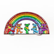 An enamel pin with five Grateful Dead bears dancing in front of a rainbow.