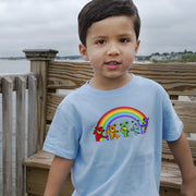 A young boy standing on a deck overlooking the beach, wearing a blue Rainbow Bears toddler tee.