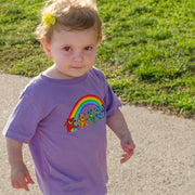 A toddler girl with a yellow flower in her hair, walking down the sidewalk, wearing a purple Rainbow Bears toddler tee.