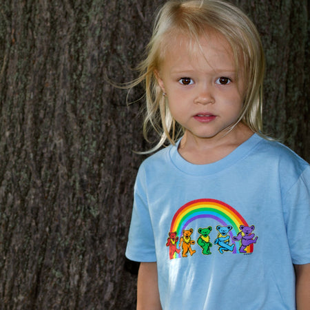A blonde toddler standing in front of a large tree, wearing a blue Rainbow Bears tshirt.