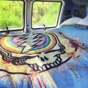 The Rainbow Splatter Stealie cotton blanket spread across a bed in the back of a van.