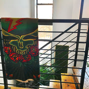 The scarlet Fire fleece blanket folded vertically and hanging over a railing at the top of wooden steps.