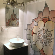 The Star Flower Shower curtain hung cozily in a bathroom next to a white sink with a plain mirror and three metal lights shining down from above it.