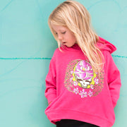 A blonde girl standing in front of a blue wall, looking down, wearing a pink Sugar Magnolia Toddler hoodie.