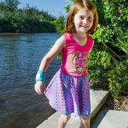 A happy girl standing next to a river lined with trees, wearing a pink Sugar Magnolia Stealie girl's tank, and a purple polka dot handmade Little Hippie skirt.