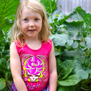 A smiling girl standing among large greenery, wearing the pink Sugar Magnolia Girl's Tank.