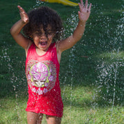 An excited girl splashing in a sprinkler, wearing a pink Sugar Magnolia Stealie girl's tank.