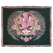 A white and green Stealie with a pink sugar magnolia flower in the center and sugar magnolia branches and flowers flowing down the sides to three central flowers at the bottom, on a dark green woven cotton blanket.