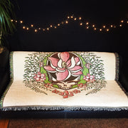 A white Sugar Magnolia cotton blanket spread on a futon in the dark, under a string of lights