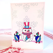 A white vertical greeting card with a snowman in an Uncle Sam hat, a red and white scarf, with a Grateful Dead lightning bolt on his stomach, two Terrapin turtles with blue and white lightening bolt shells dancing around him, and large snowflakes in the background