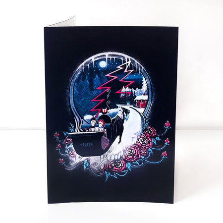 A black vertical greeting card with a skeleton couple riding a horse-drawn sleigh down a snowy path into a Steal Your Face skull, towards a red house in the woods. The skull is nestled into a bed of roses partly hidden by the sleigh and snow.