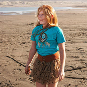 Smiling red haired girl, standing on a beach wearing aGrateful Dead Steal Your Face skull in a dream catcher with white and blue feathers hanging from it, on a turquoise youth tshirt, and a brown skirt
