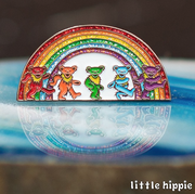 The Rainbow Bears pin standing on a shiny blue agate slice.