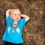 Toddler boy laying on the ground, looking at the sky, wearing a turquoise Grateful Dead Steal Your Face Dreamcatcher toddler tshirt