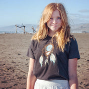 Red haired girl with a knowing smile, standing on a beach wearing a Grateful Dead Steal Your Face skull in a dream catcher with white and blue feathers hanging from it, on a dark grey youth tshirt and a white skirt